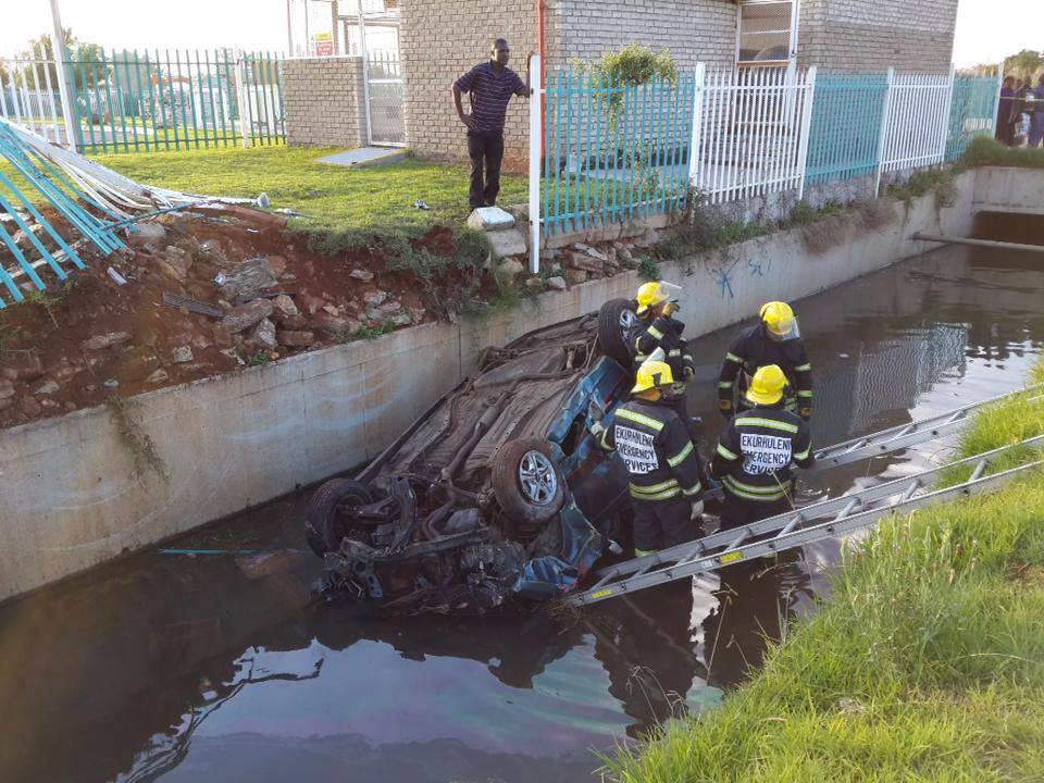 The car that crashed through a business perimeter fence and landed on it's roof in a nearby canal. One person was killed and another injured. Image courtesy ER24 Paramedics