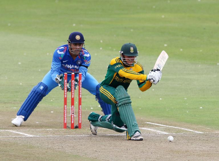 India's cricketer MS Dhoni (left) looks on as Quinton de Kock of South Africa bats during their one day international in Durban on December 8, 2013