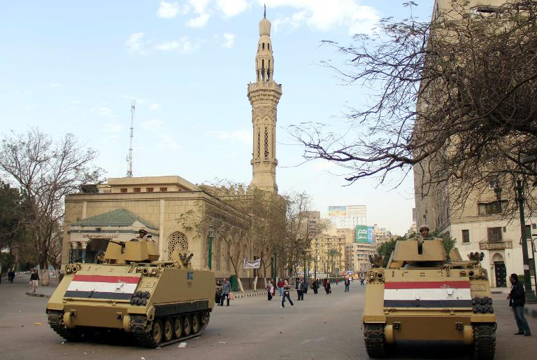Egyptian military vehicles are positioned near Cairo's Tahrir square on January 26, 2014 the day after thousands gathered in the square chanting slogans backing General Abdel Fattah al-Sisi, while police clashed with Islamists and activists elsewhere