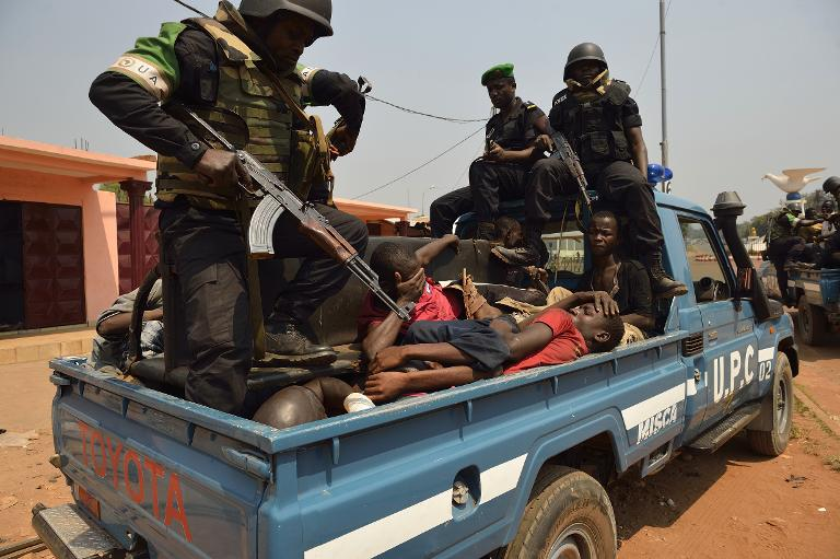 Congolese soldiers from the African-led International Support Mission to the Central African Republic (MISCA) sit on a vehicle with looters after they arrested them in a street in Bangui on January 12, 2014 PHOTO: AFP