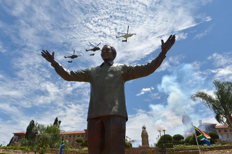 Helicopters carrying the South African flag fly over a 9-meter bronze statue of former president Nelson Mandela which was unveiled on December 16, 2013 in Pretoria. PHOTO: AFP