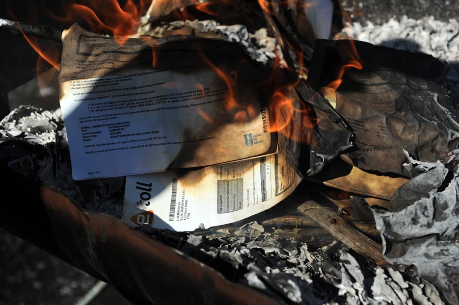 E-toll objectors burn their e-toll bill notifications, 25 January 2014, at the Portuguese Hall in Joburg South, before taking part in a mass protest drive along the tolled highways. Picture: Michel Bega
