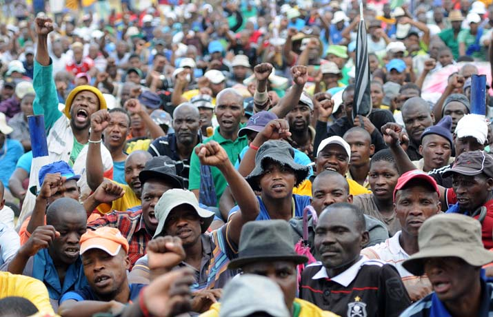FILE PICTURE: A group of mine workers listen to their president  Joseph Mathunjwa's address at Wonderkop stadium next to Lomin mine in Marikana outside Rustenburg, where AMCU union members  where meet ing after downing their tools demanding an increase of R12500 a month salary. Picture: Nigel Sibanda