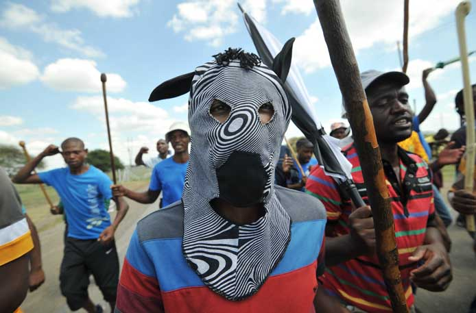 FILE PICTURE: A man wears a zebra-mask as striking miners chant slogans while marching to Wonderkop Stadium near Lonmin's platinum mine in Marikana on January 23, 2014. Up to 80,000 workers at Impala Platinum, Anglo American Platinum and Lonmin mines will embark on an indefinite strike from early Thursday.  AFP PHOTO / ALEXANDER JOE