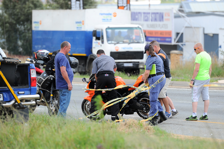 FILE PICTURE: Members of the SAPS and JMPD attend to a crime scene where a biker was shot dead in an apparent road rage incident, 14 February 2014, in Kya Sands, on Malibongwe Drive. Allegedly the biker and a motorist faced off, with both men armed and discharging their guns. The motorist was also shot and is in a critical condition in hospital. Picture: Michel Bega