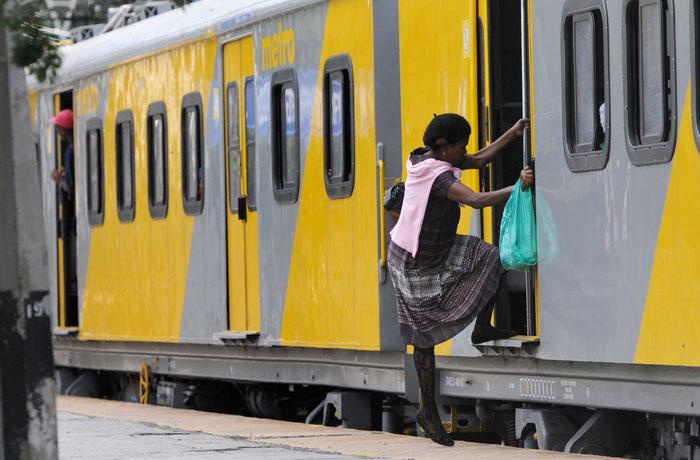 A Metrorail commuter gets on a train. Picture: Nigel Sibanda.