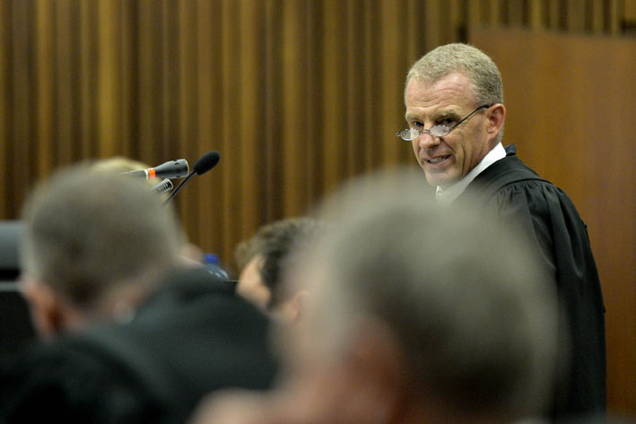 Prosecutor Gerrie Nel reads out the charges during the appearance of double amputee and Paralympain Oscar Pistorius in the North Gauteng High court in Pretoria, South Africa, Monday, 3 March 2014. Pistorius is accused of the murder of Reeva Steenkamp on February 14, 2013. He faces two charges; murder and contravention of the Firearms Control Act. Photo by Herman Verwey - POOL