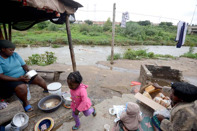 Woman and children work and play outside a dwelling in Alexandra on the Jukskei River, 10 March 2014.  Heavy rains that have fallen in the area have left many residents at risk.  Picture: Tracy Lee Stark