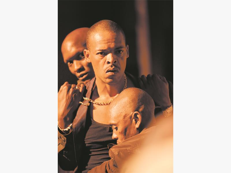 SUSPICIOUS. Israel Makoe, centre, has to be restrained by Warren Masemola, left, and Percy Matsemela, right.