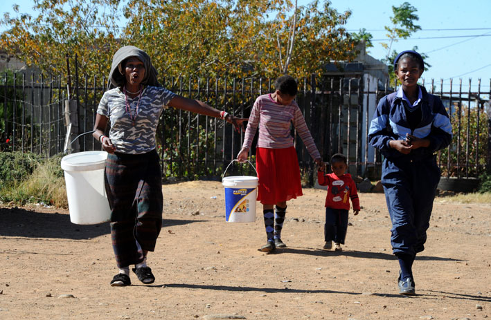 A woman (L) complains as she walks with others to queue for water in the township of Boitumelong in Bloemhof in North West on Thursday, 29 May 2014. North West health department spokesman Tebogo Lekgethwane said Bloemhof's water source had been contaminated.