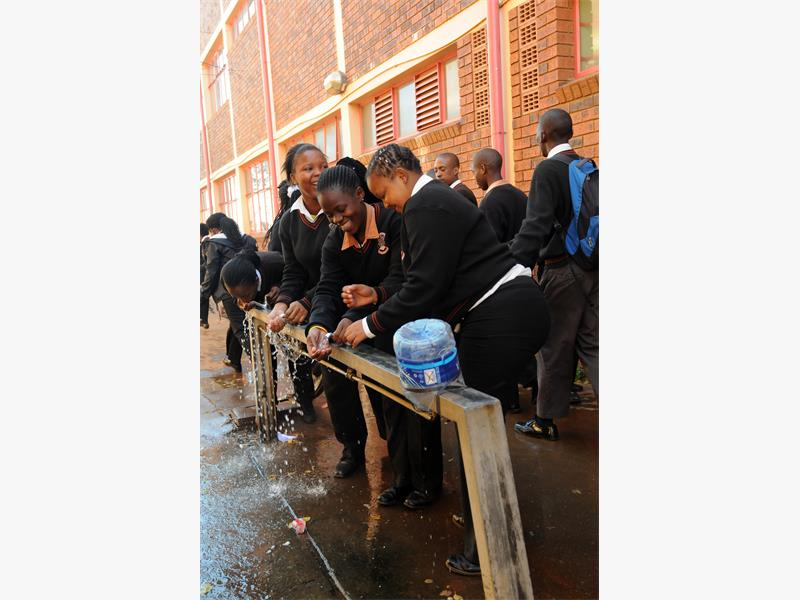 Buhlebuzile Secondary School pupils in Thokoza drink water at a communal tap in Johannesburg, 15 May 2014,  . Picture: Nigel Sibanda
