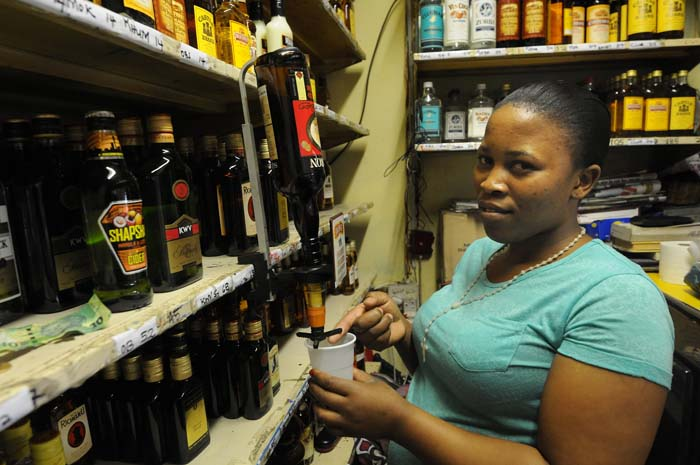 Joalane Mokoena pours launch time drinks at a tavern known as '' ga Magogo'' opposite Bara taxi rank in Johannesburg,  28 May 2014. The tavern has been serving patrons for over  40 years. Picture: Nigel Sibanda