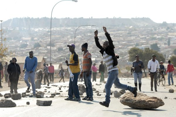 A young man jumps of a rock during a protest in Mofolo North, Soweto, 17 June 2014. Residents blocked roads and burnt tyres complaining of repeated instances of electricity outages without any notice from the municipality. Picture: Refilwe Modise