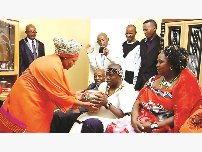 Sindilie Mathonsi is given traditional Xhosa beer by his bride's family during his traditional wedding.