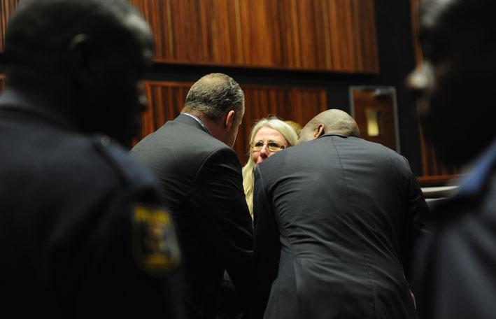 FILE PICTURE: Czech fugitive Radovan Krejcir (L) is seen with his lawyer Annelene van den Heever while policemen keep an eye at the High Court in Johannesburg, sitting in Palm Ridge, Monday, 21 July 2014. Krejcir, Desai Luphondo, Warrant Officers Samuel