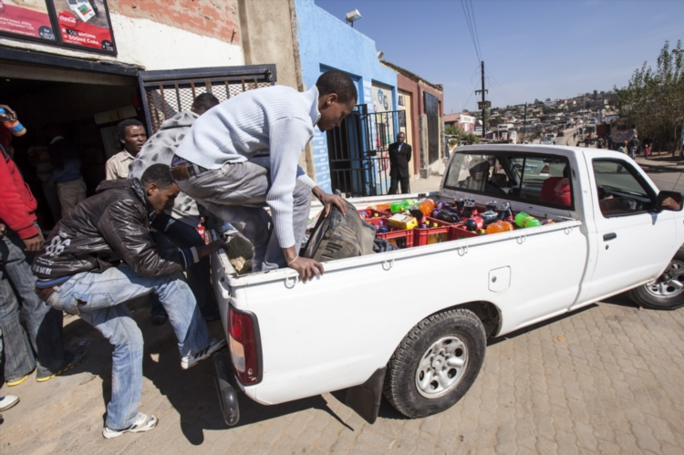 FILE PICTURE:  Foreign shop owners load their stock onto a bakkie. (Photo by Gallo Images / Daniel Born).