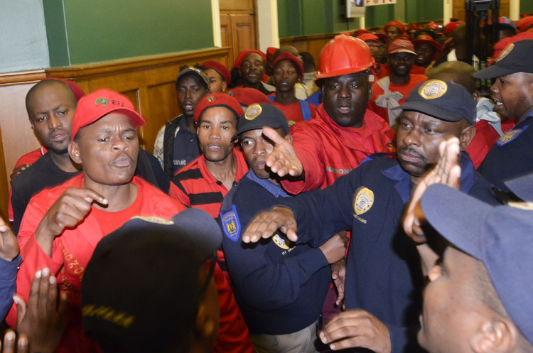 Members of the Economic Freedom Fighters argue with police after members of the party forced their way into the Gauteng Legislature building in Johannesburg CBD, 22 July 2014, during a protest over the ruling against the wearing of red overalls in the building. Picture: Alaister Russell