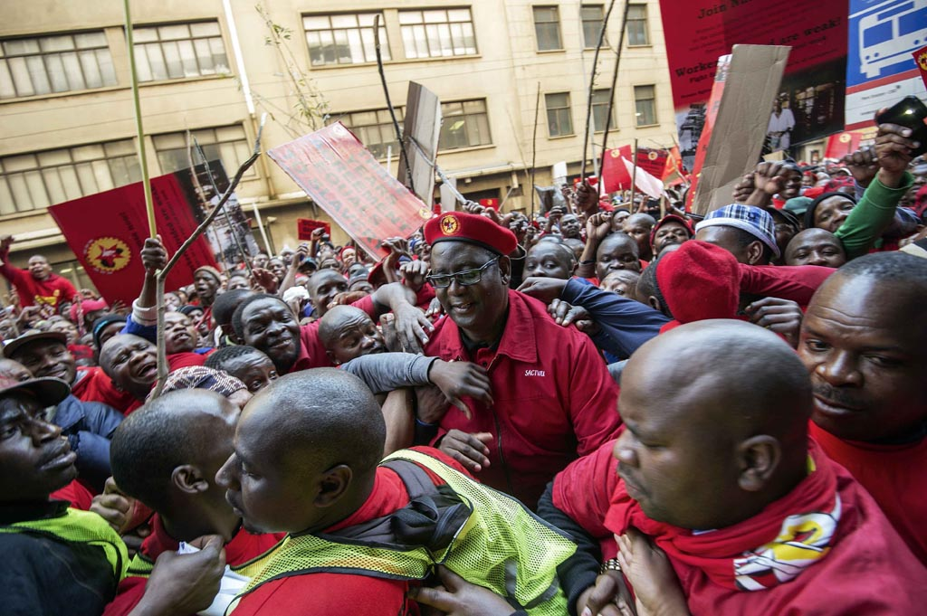 FILE PICTURE: Cosatu Secretary General Zwelinzima Vavi (C) is surrounded by supporters as he arrives to address striking members National Union of Metalworkers (NUMSA) protesting in front of the Metal Industries House on the first day of a nationwide strike called by NUMSA in Johannesburg CBD on July 1, 2014. AFP PHOTO/GIANLUIGI GUERCIA