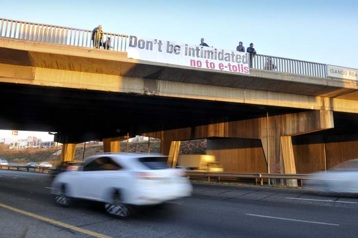 Anti E-Toll activists, who prefer not to be named, hang signs above the R24 highway in Kempton Park, Johannesburg, 01 July 2014, in protest over the controversial tolling system. Gauteng Premier David Makhura announced during the State of the Provence Address that he would be setting up a panel to review the tolling system. Picture: Alaister Russell