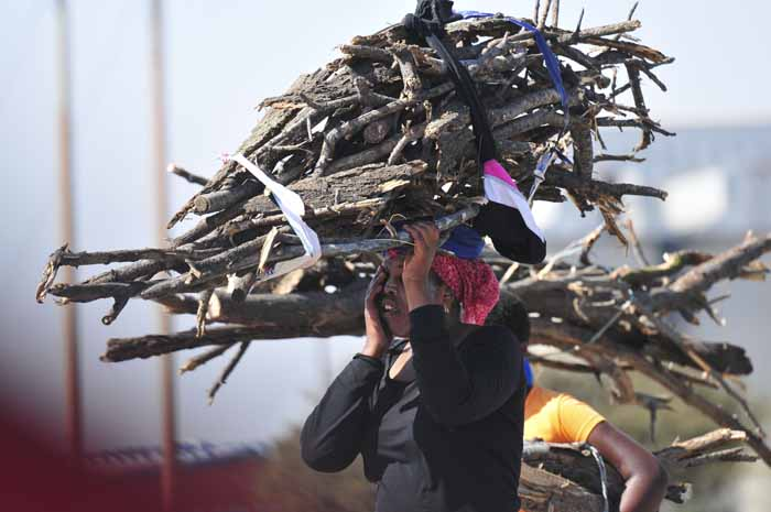 A woman carries wood back to her home in Marikana, 14 July 2014, in the North West Province. Residents are seeing an increase in local trade following the five month mine worker strike in the area. Picture: Alaister Russell