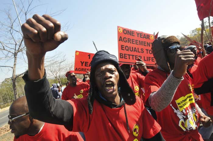 FILE PICTURE: Striking National Union of Metalworkers of South Africa (Numsa) members hold placards during a picket, 02 July 2014, outside the Eskom offices in Sunninghill Johannesburg. Numsa members are demanding 12 percent wage increase and R1000 housing allowance. Picture: Alaister Russell