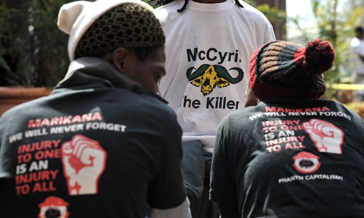 """People show T-shirts bearing the words """"McCyril the killer"""" and """"Marikana - we will never forget"""" while attending the Farlam Commission of Inquiry in Centurion, Pretoria on Monday, 11 August 2014 where Deputy President Cyril Ramaphosa was testifying. Some T-shirts had a drawing of a buffalo head. These were references to Ramaphosa reportedly once unsuccessfully bidding up to R19.5 million for a buffalo cow, and his ownership of the McDonald's franchise in South Africa. The commission is investigating the deaths of 44 people during strike-related violence at Lonmin's platinum mining operations at Marikana, near Rustenburg in the North West, in August 2012.Picture: SAPA stringer"""