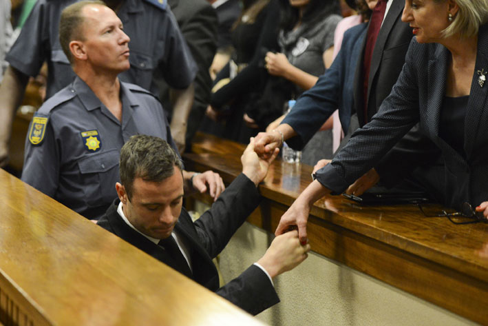 Oscar Pistorius holds the hands of family members as he is taken down to the holding cells after being sentenced to five years imprisonment for the culpable homicide killing of his girlfriend Reeva Steenkamp at the high court in Pretoria, Tuesday, 21 October 2014. Picture: Herman Verwey/Media24/Pool