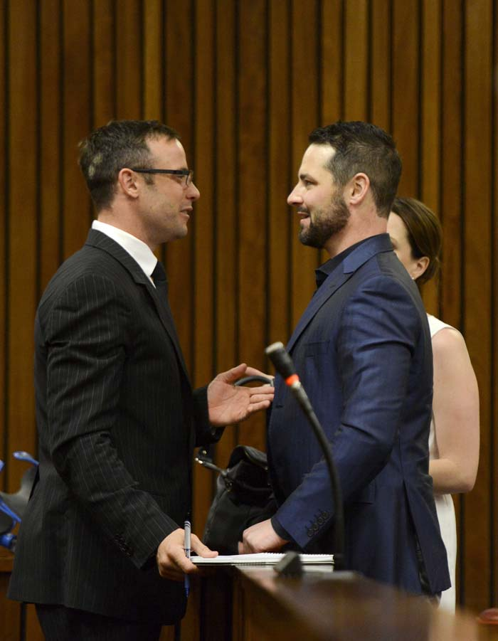 South African Paralympic athlete Oscar Pistorius (L) talks with his brother Carl (R) on day two of sentencing procedures at the High Court in Pretoria, South Africa, 14 October 2014. Judge Thokozile Masipa found South African Paralympic athlete Oscar Pistorius not guilty of the murder of Reeva Steenkamp in February 2013 but guilty of culpable homicide.  EPA/HERMAN VERWEY / POOL