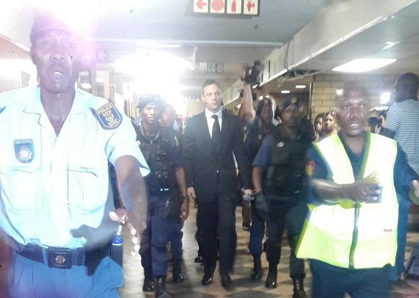 Oscar Pistorius is guarded by a heavy police presence arrives for his sentencing at court in Pretoria. Picture: Yadhana Jadoo.