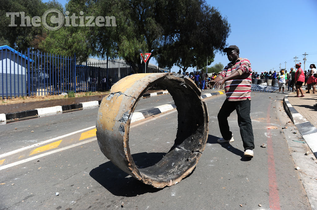 Newclare residents roll a section of concrete pipe down a road, 6 October 2014, during a protest for better services and housing. The protesters earlier set fire to the train station and nearby vehicles. One person was shot dead in the protests. Picture: Michel Bega