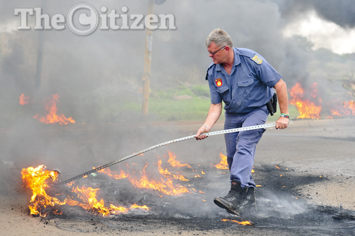 FILE PICTURE: Police remove rocks and burning tyres from the road which enraged residents lit  in an attempted landgrab at Nellmapius on 12 November 2014. Picture: Christine Vermooten