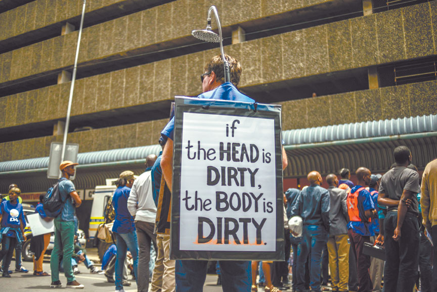 A Democratic Alliance (DA) party surpporter wears a banner and a showerhead on 13 November 2014, looking like President Jacob Zuma's depiction often made by South African cartoonist Jonathan Shapiro, during a DA protest outside police headquarters in Pretoria to demand that the national police commissioner do more to lower the nation's crime rate. AFP PHOTO/MUJAHID SAFODIEN