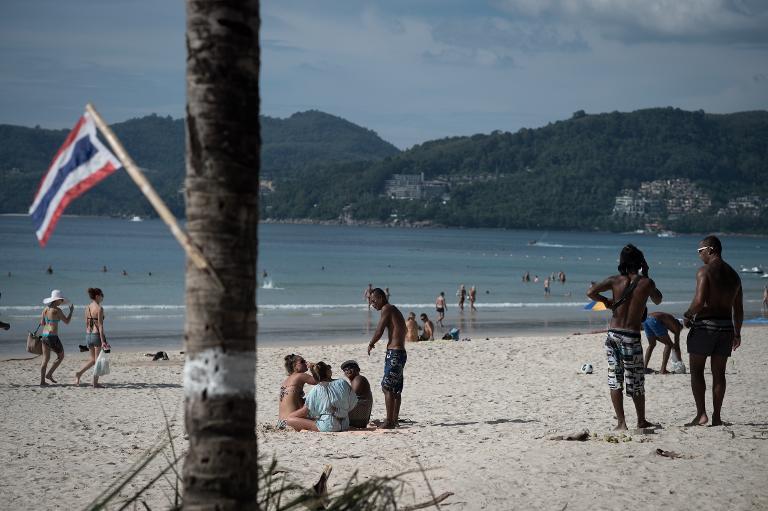 AFP / Nicolas Asfouri<br />People relax on Patong beach in Phuket, December 4, 2014