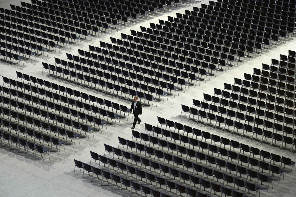FILE PICTURE: A man walks between empty seats. AFP PHOTO / CHRISTOF STACHE