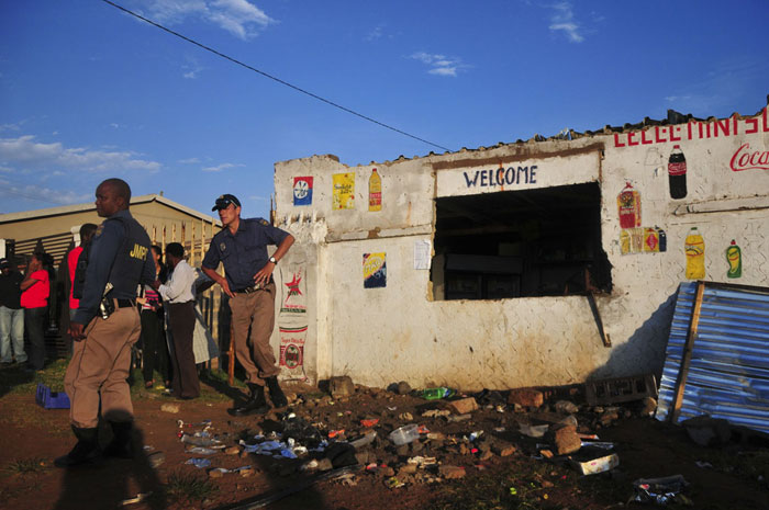 FILE PICTURE: Members of the police guard a shop owned by foreign nationals after residents looted its contents, 21 January 2015, in Braamfischerville, Soweto. Residents have been targeting foreign owned shops in the area following a shooting incident in Snake Park, near Dobsonville where a foreign national allegedly shot dead a teenager who was trying to rob the shop. Picture: Alaister Russell