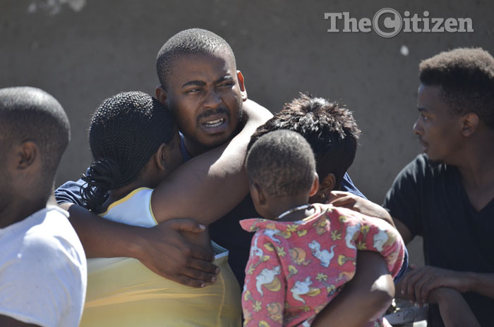 """FILE PICTURE: Skwatta Kamp member Nkululeko """"Flabba"""" Habedi's brother Tshepang Hadebi hugs family members outside their family home, 09 March 2015 in Alexandra Township, Johannesburg. Flabba was allegedly stabbed to death by his girlfriend in the early hours of the morning. Picture: Alaister Russell"""