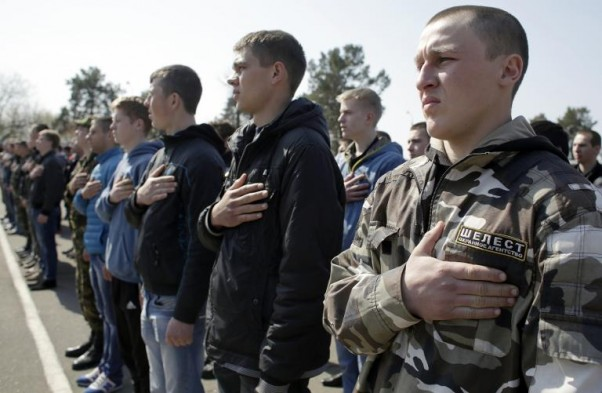 AFP / Anatolii Stepanov<br />Ukrainian army recruits hold their hands over their hearts as the national anthem is played during a farewell ceremony in Kiev on April 16, 2015
