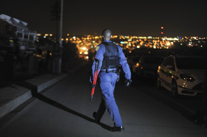 FILE PICTURE: A policeman walks out of the Madala hostel with bolt cutters. Picture: Alaister Russell