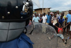 Burundian youth face police officers during a protest against President Pierre Nkurunziza's bid for a third term in Musaga, on the ourskirts of Bujumbura, on April 29, 2015.  AFP PHOTO / SIMON MAINA