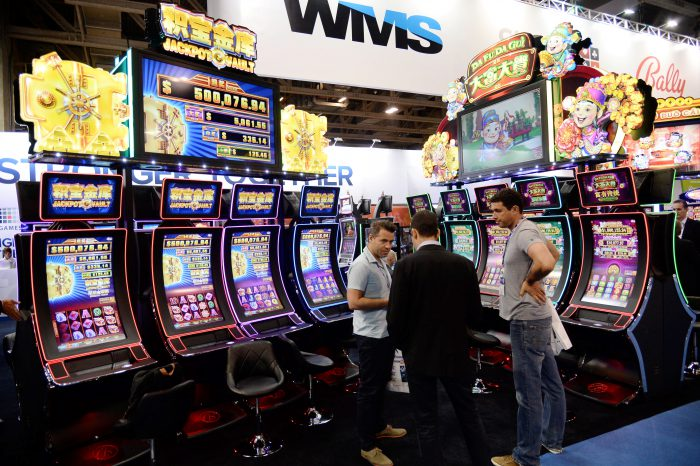 Visitors talk next to slot machines during the Global Gaming Expo (G2E) Asia in Macau, China, 19 May 2015. | AFP