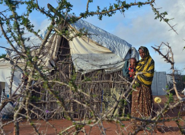 A somali refugee woman with her child stand in their compound at Hagadera sector of the Dadaab refugee camp, north of the Kenyan capital Nairobi, on April 29, 2015.  AFP PHOTO/Tony KARUMBA