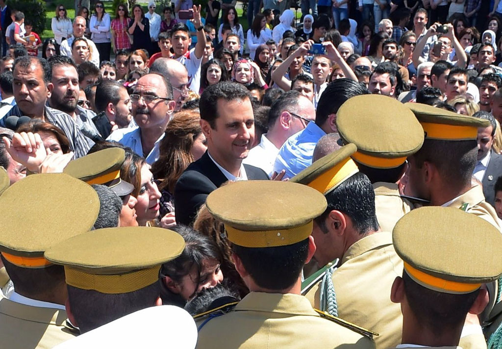 A handout picture released by the Syrian Arab News Agency (SANA) on May 6, 2015, shows President Bashar al-Assad (C-L) standing amid the crowd during an appearance at a school in the capital Damascus on Syria's Martyrs Day. Assad said that setbacks are a normal part of war and do not mean the conflict is lost, in his first comments after several regime defeats. AFP PHOTO / HO / SANA