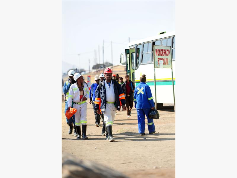 Lonmin mine workers disembark from a staff bus next to Wonderkop Stadium in North West, 26 June 2015, a day after president  Jacob Zuma delivered Marikana report. Picture: Nigel Sibanda