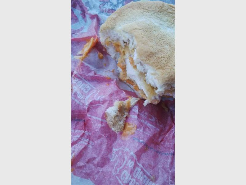 A disgruntled KFC customer posted this picture on Facebook after she found chewed bubble gum stuck onto the bun of her Crunch Burger. Pic: Danri Kruger/Facebook