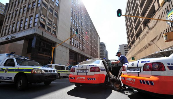 JMPD sniffer dogs get put back in the car after searching The Star newspaper building on Sauer street in the Johannesburg CBD, 14 September 2015. A phonecall was recieved saying there was a bomb in the building, prompting an evacuation. Police searched the building with sniffer dogs and concluded that it was a hoax. Picture: Neil McCartney