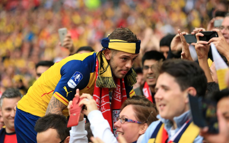 Arsenal's Jack Wilshere poses for photographs in the stands for fans