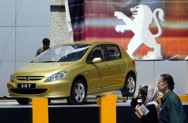 """AFP/File / Behrouz Mehri<br />An Iranian couple passing by a French Peugeot 307, produced by Iranian """"Iran Khodro"""" company, during a 2004 car fair in Tehran"""
