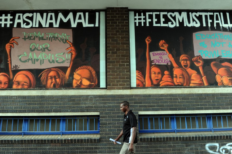 A pedestrian walks past street art in Braamfontein, on the side of the building that houses the Stevenson Gallery, 20 January 2016. The art reads