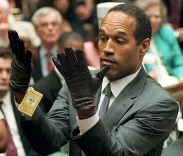 """(FILES) This file photo taken on November 30, 1995 shows former US football player and actor O.J. Simpson looking at a new pair of Aris extra-large gloves that prosecutors had him put on during his double-murder trial in Los Angeles.  Twenty years ago, it was the """"Trial of the Century"""" watched by millions of Americans. Now the O.J. Simpson murder trial is back on television, exploiting a growing obsession with true-life crime mysteries. The first episode in the 10-part """"The People v. O.J. Simpson: American Crime Story"""" premiered on FX,on February 2, 2016 offering a dramatized behind-the-scenes look at how America's football hero was charged but acquitted of murdering his ex-wife Nicole Brown and her friend Ronald Goldman.  / AFP / VINCE BUCCI"""