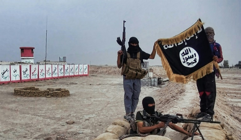 Welayat Salahuddin/AFP/File / - Militants of the Islamic State group posing with the trademark Jihadists flag after they seized an Iraqi army checkpoint in the northern province of Salahuddin in June 2014